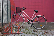 A locked bike in a rack next to dog faeces outside an apartment building in Wedding, a north-western district of Berlin. The pink bicycle is locked to the red rack against a pink tiled wall, standing on cobbles in a more downmarket area, home to non-germans and immigrants.