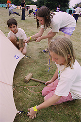 Group of children putting up tent in campsite using mallets and pegs during environmental awareness camp,