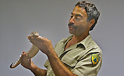 New Jersey Parks and Forestry ranger holds and shows children large lizard at Cape May park nature center