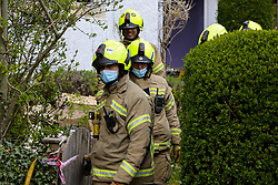 © Licensed to London News Pictures. 16/04/2021. London, UK. Firefighters outside a house on Springfield Avenue in Hornsey, North London where a woman in her 70s died following a fire. The fire broke out early this morning and it took 40 Firefighters, three hours to suppress the flames. The woman has not yet been identified and the cause of the fire is under investigation by the Fire Brigade. Photo credit: Dinendra Haria/LNP