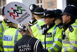 © Licensed to London News Pictures. 30/11/2011. London, UK. A man carrying a 'Coalition of Resistance' banner talks to police officers . Workers and Union members gather in central London today (30/11/2011) to take part in national strike action. Up to two million public sector workers are staging a strike over pensions in what is set to be the biggest walkout for a generation.  Ben Cawthra/LNP