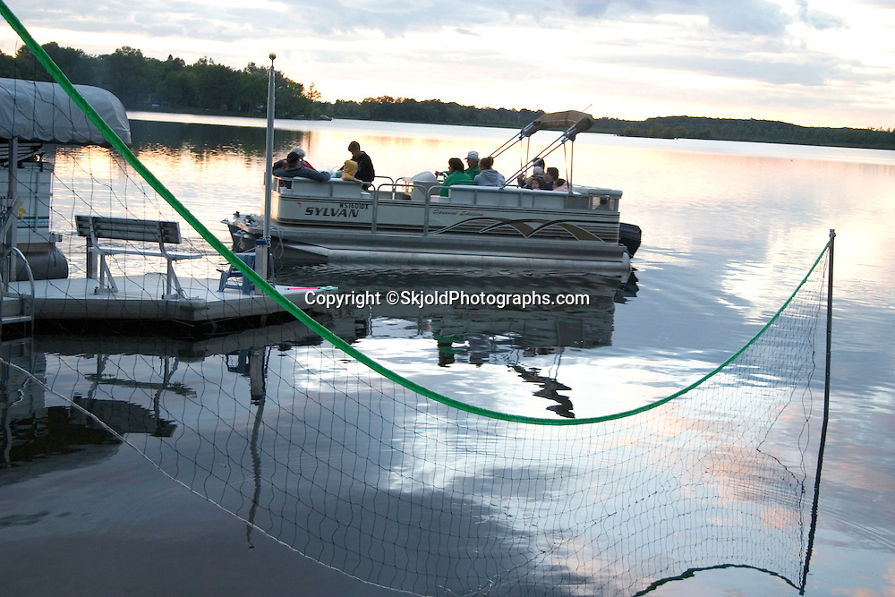 Family on an evening pontoon boat ride framed by water volleyball net. Kettle Moraine Lake Campbellsport Wisconsin USA