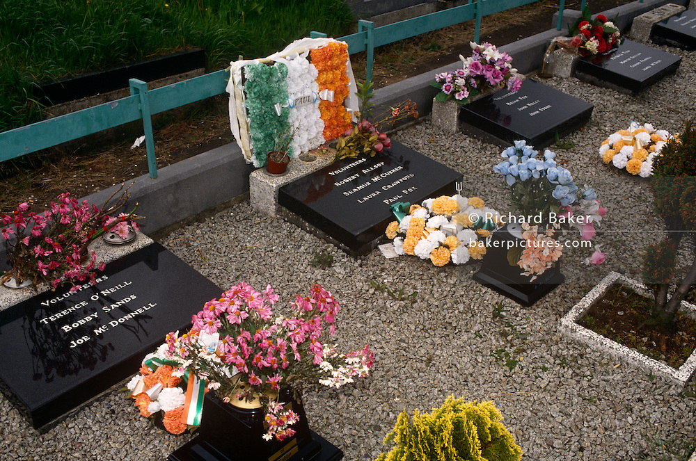 "The graves of Irish Republican hunger strikers in Milltown Cemetery, Belfast. Their roll-call of names are on stones laid o the ground including that of Bobby Sands, the elected MP. The five-year protest during The Troubles began as the blanket protest in 1976, when the British government withdrew Special Category Status for convicted paramilitary prisoners. In 1978, after a number of attacks on prisoners leaving their cells to ""slop out"", the dispute escalated into the dirty protest, where prisoners refused to leave their cells to wash and covered the walls of their cells with excrement. The second hunger strike took place in 1981 and was a showdown between the prisoners and the Prime Minister, Margaret Thatcher. The strike was called off after ten prisoners had starved themselves to death?including Sands, whose funeral was attended by 100,000 people,"