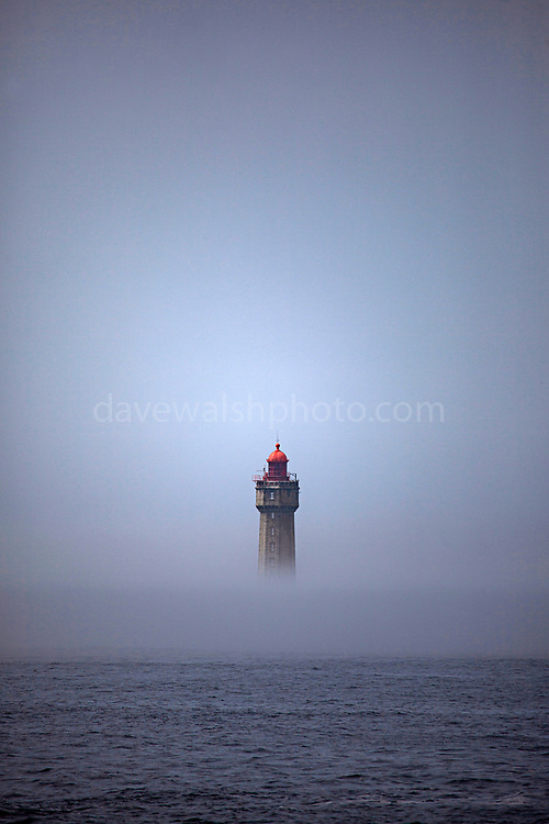 The dramatic La Jument lighthouse, shrounded in summer fog, off the coast of the Ile d'Ouessant, Brittany. The iconic 47-metre high lighthouse was built between 1904 and 1911 in a particular treacherous part of the Brittany coastline.