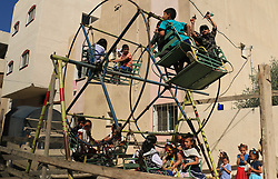 June 15, 2018 - Bureij, Gaza Strip - Palestinian children enjoy the first day of Eid al-Fitr holiday which marks the end of the Muslim holy month of Ramadan, in al-Bureij in the center of Gaza Strip on June 15, 2017. Eid al-Fitr marks the end of Muslim's holy fasting month of Ramadan when faithfuls abstain from eating, drinking, smoking and sexual activities from dawn to dusk  (Credit Image: © Mahmoud Khattab/APA Images via ZUMA Wire)