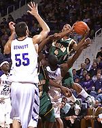 Cleveland State guard Joe Davis (4) drives in for a basket over Kansas State's David Hoskins (15) and Jason Bennett (55) in the first half at Bramlage Coliseum in Manhattan, Kansas, December 5, 2006.  K-State beat the Vikings 93-60.<br />