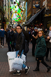 London, December 24 2017. Crowds grow in London's west end on Christmas eve as last minute shoppers hunt for gifts. PICTURED: A man carries shopping bags along Carnaby Street. © SWNS