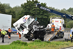 © Licensed to London News Pictures. 26/08/2017. Milton Keynes, UK. REMAINS OF MINIBUS PICTURED RIGHT UNDERNEATH TARPAULIN. The sceneon the M1 motorway near Newport Pagnell after a crash involving a minibus and two lorries. Police say that several people are dead and four others have been taken to hospital after the accident on the southbound carriageway in the early hours of this morning. Photo credit: Ben Cawthra/LNP