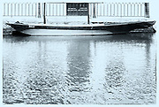 Boat on Venetian canal with reflections in water, Venice, Italy