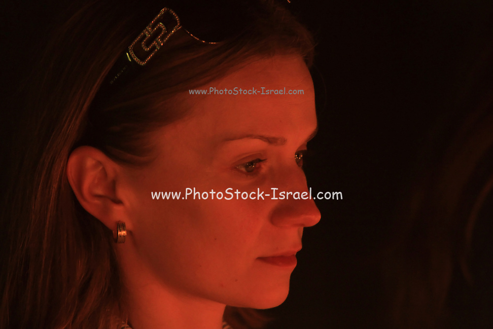 portrait of woman faces lit by candle light praying in a church