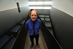 "© Licensed to London News Pictures. 25/09/2018. LONDON, UK. Artist Richard Wilson poses with his work ""20:50"", 1987, steel tanks full of sump oil. Preview of ""Space Shifters"" at the Hayward Gallery, an exhibition which features artworks by 20 leading international artists that disrupt the visitor's sense of space and alter their perception of their surroundings.  The show runs 26 September to 6 January 2019.  Photo credit: Stephen Chung/LNP"