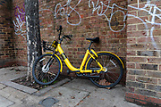 An Ofo dockless sharing bicycle left on the street in south London, England on November 23, 2018 . The increasing use of dockless sharing bikes in London comes after two Chinese companies, Ofo and Mobike, launched their mobile app-based service in the capital last year.