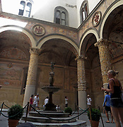 The Palazzo Vecchio, Florence, Italy. This massive, Romanesque. The first courtyard was designed in 1453 by Michelozzo. In the lunettes, high around the courtyard, are crests of the Church and City Guilds. In the centre, the porphyry fountain is by Battista del Tadda.