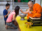 16 NOVEMBER 2013 - BANGKOK, THAILAND: A monk blesses people Wat Saket during the annual temple fair. Wat Saket is on a man-made hill in the historic section of Bangkok. The temple has golden spire that is 260 feet high which was the highest point in Bangkok for more than 100 years. The temple construction began in the 1800s in the reign of King Rama III and was completed in the reign of King Rama IV. The annual temple fair is held on the 12th lunar month, for nine days around the November full moon. During the fair a red cloth (reminiscent of a monk's robe) is placed around the Golden Mount while the temple grounds hosts Thai traditional theatre, food stalls and traditional shows.    PHOTO BY JACK KURTZ