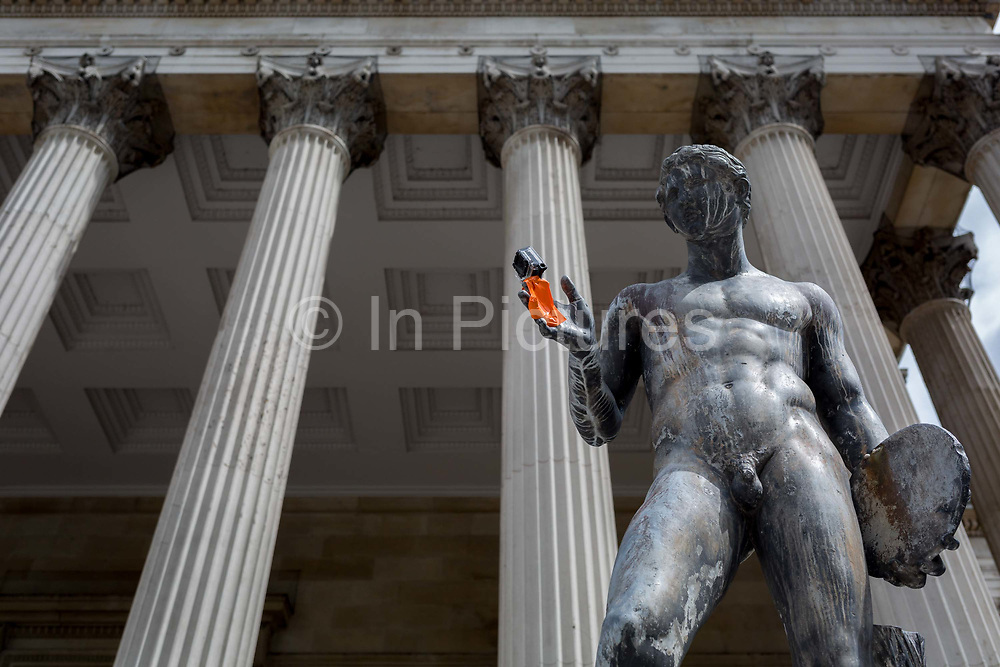 A classical statue with a GoPro camera taped to one hand stands beneath Corinthian columns of the Main Building at University College London UCL, on 3rd August 2017, in London, England.