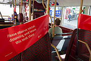 A banner of social distancing tape is stretched across two bus seats so that passengers are deterred from sitting too close to one another during the coronavirus pandemic, on 8th August 2020, in London, England.