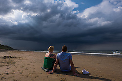 © Licensed to London News Pictures.05/07/15<br /> Saltburn by the Sea, UK. <br /> <br /> A couple sit in evening sunshine and look on as storm clouds pass over the north sea off the coastline at Saltburn by the Sea. <br /> <br /> Photo credit : Ian Forsyth/LNP