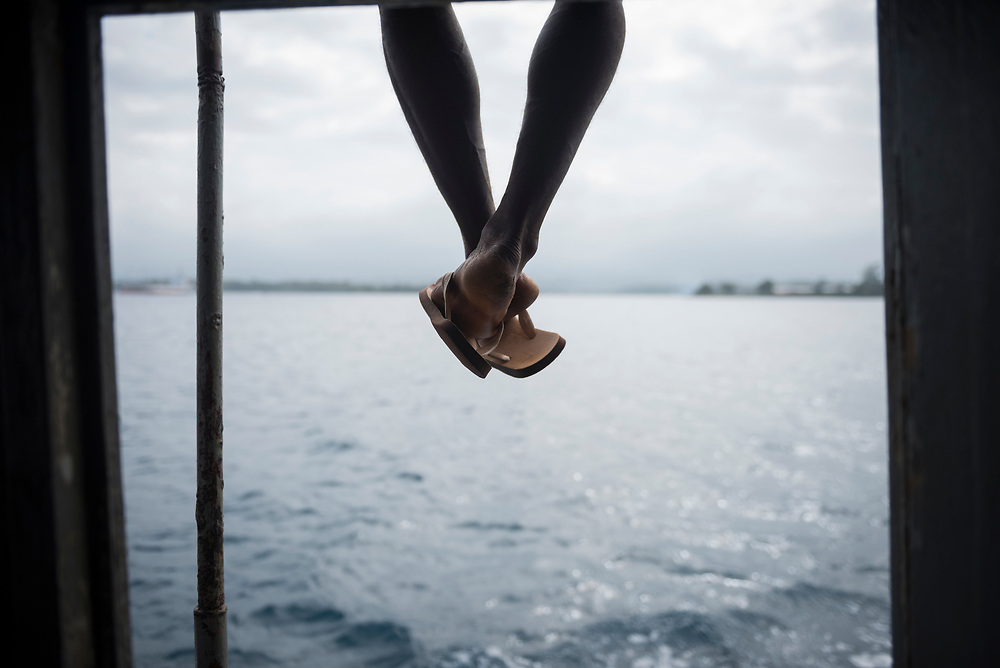 A Papua New Guinean man sits on top of a boat entering the harbor in Madang, Papua New Guinea. Flip flops are standard footwear in Papua New Guinea
