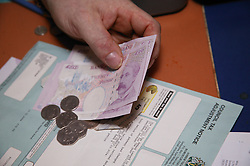 Close up of hand counting money to pay bills with,