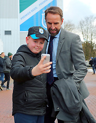 A young Huddersfield Town fan takes a selfie with England Manager Gareth Southgate ahead of the Premier League match at the John Smith's Stadium, Huddersfield.