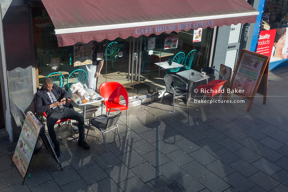 A local man sits in sunshine outside the Cafe House Restaurant on the Walworth Road in Southwark, on 25th February 2019, in London, England.