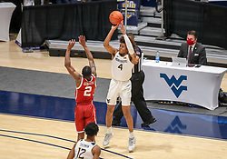 Feb 13, 2021; Morgantown, West Virginia, USA; West Virginia Mountaineers guard Miles McBride (4) shoots a three pointer over Oklahoma Sooners guard Umoja Gibson (2) during the first half at WVU Coliseum. Mandatory Credit: Ben Queen-USA TODAY Sports