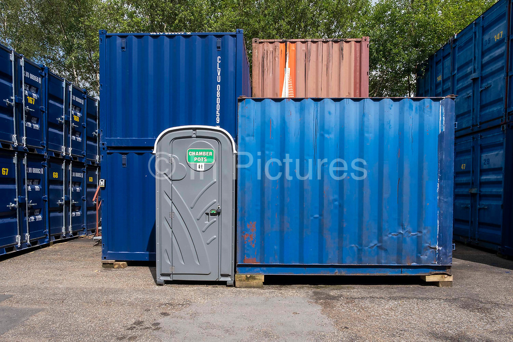 A portable toilet for self-storage customers stands next to rows of stacked metal storage shipping containers in a self-storage depot on 17th June 2019 in Aldershot, Hampshire, United Kingdom.