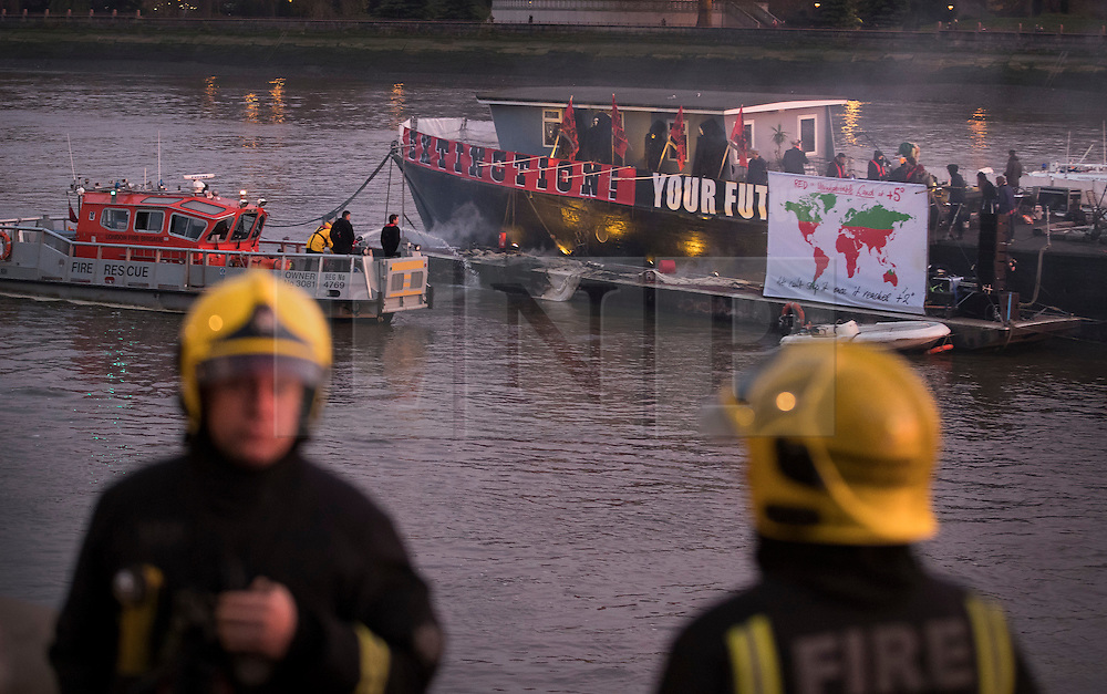 """© Licensed to London News Pictures. 26/11/2016. London, UK. A Fire Service riverboat extinguishes a fire started by Joe Corre, the son of former Sex Pistol manager Malcolm McLaren and Vivienne Westwood as he burns his personal collection of Sex Pistols punk memorabilia on a boat in the Thames in Chelsea. Earlier this week Joe Corre said that punk has become nothing more than a """"McDonald's brand ... owned by the state, establishment and corporations"""". His collection is estimated to be worth £5 million. Photo credit: Peter Macdiarmid/LNP"""