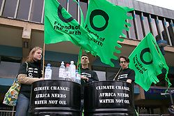 Group of Friends of the Earth supporters staging protest using oil drums and flags,