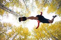 Young man trail running during fall near Fallen Leaf Lake, CA.