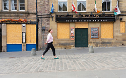 Edinburgh, Scotland, UK. 16 June, 2020. As shops open in England, Scottish shops and businesses remain closed, Streets are empty and pubs and shops are still closed with many boarded up. Bars might be allowed to open outside areas at end of week but currently they are oonly-permitted to serve drinks to takeaway. Pictured; Boarded up pubs on the Grassmarket in the Old Town. Iain Masterton/Alamy Live View.