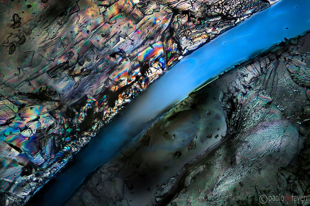 """A view at the microscope of salt and sugar crystals on glass in polarized light. The """"river"""" is actually a crack in the mass of sugar and salt, unveiling the glass beneath. A microscopic grand canyon in a colorful desert."""
