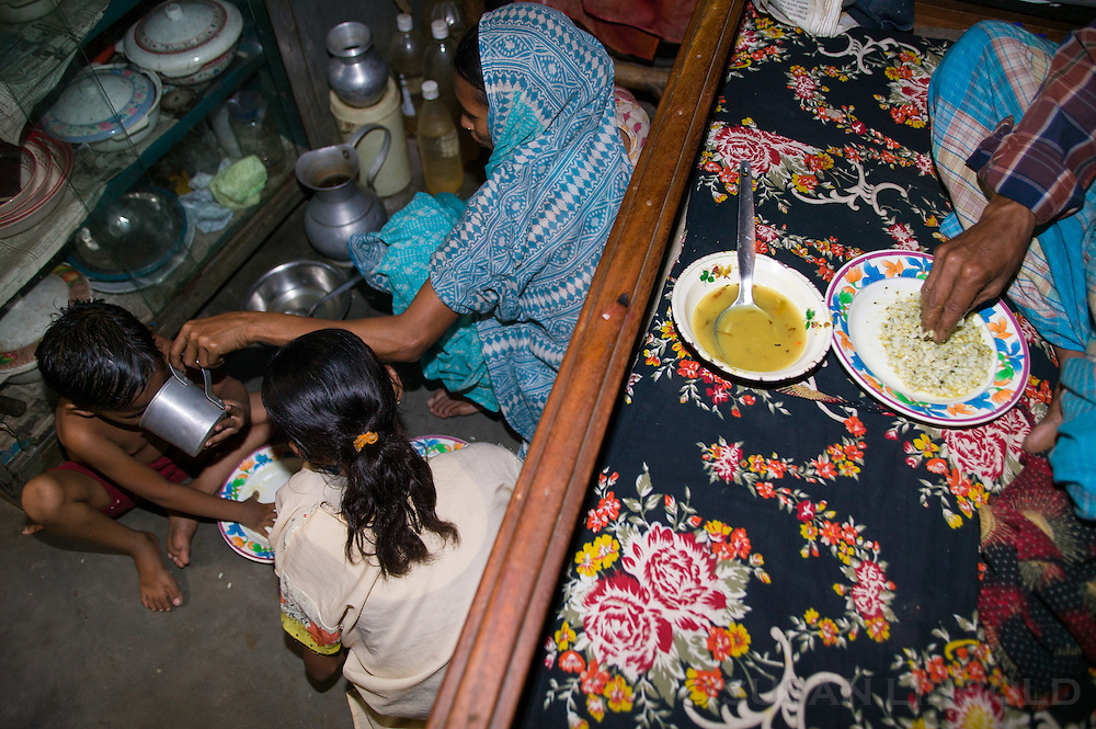 The family eating lunch. Jalal's wife and daughters eat on the floor at the foot of the bed, while Jalal usually eats on the bed. This space is also where Jalal sleeps at night. His wife and four daughters sleep on the bed.
