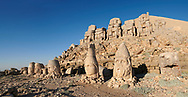Statue heads, from right,  Eagle, Herekles, Apollo, Zeus, Commagene, Antiochus, & Eagle, with headless seated statues in front of the stone pyramid 62 BC Royal Tomb of King Antiochus I Theos of Commagene, east Terrace, Mount Nemrut or Nemrud Dagi summit, near Adıyaman, Turkey .<br /> <br /> If you prefer to buy from our ALAMY PHOTO LIBRARY  Collection visit : https://www.alamy.com/portfolio/paul-williams-funkystock/nemrutdagiancientstatues-turkey.html<br /> <br /> Visit our CLASSICAL WORLD HISTORIC SITES PHOTO COLLECTIONS for more photos to download or buy as wall art prints https://funkystock.photoshelter.com/gallery-collection/Classical-Era-Historic-Sites-Archaeological-Sites-Pictures-Images/C0000g4bSGiDL9rw