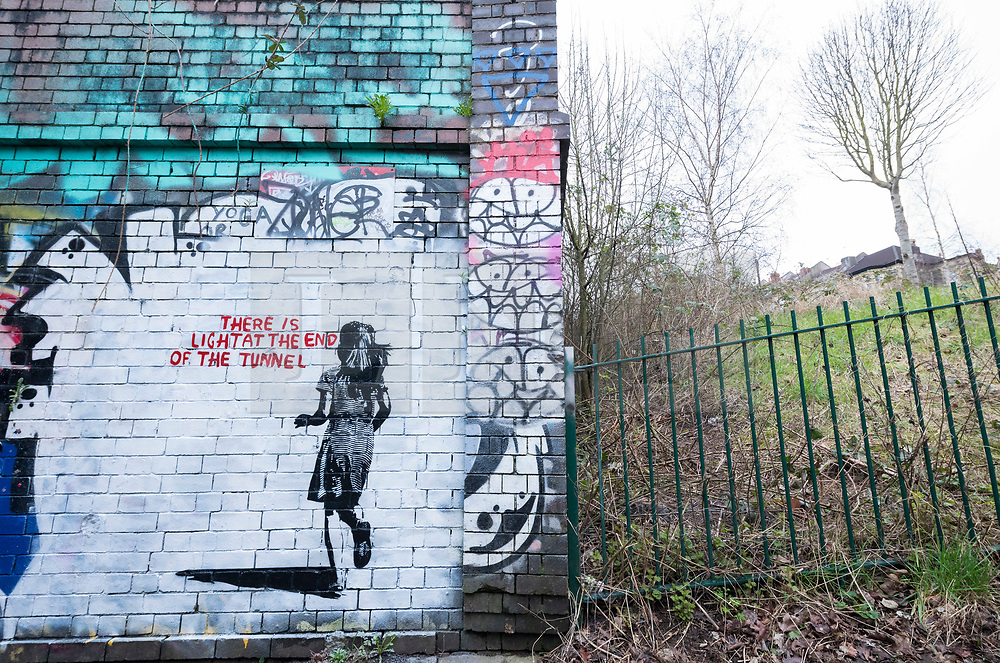 """© Licensed to London News Pictures; 14/03/2021; Bristol, UK. A mural in the style of Banksy with an image of a girl and with the words """"There is light at the end of the tunnel"""", is seen next to a tunnel under the railway off Muller Road in Bristol. According to some locals it has been painted very recently, perhaps early this morning. Banksy often comments on current events, and if the piece is by Banksy it could be a reference to the end of the covid-19 coronavirus pandemic, or to social movements such as #MeToo, Black Lives Matter, or Reclaim the Streets. Photo credit: Simon Chapman/LNP."""