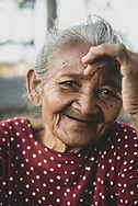 """Nusa Penida, Indonesia - September 27, 2017: Portrait of Dadong Nengah (""""Grandmother Nengah""""), who I met as she sat by the sea with several grazing cows."""