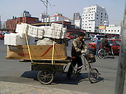 a fully loaded tricycle in the street of Beijing China