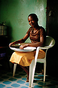 Girl sifts corn flour preparing ugali, a traditional African meal. Kampala, Uganda.