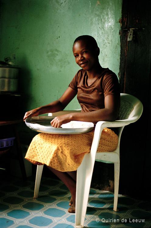 Girl sifts maize flour. Kampala, Uganda.
