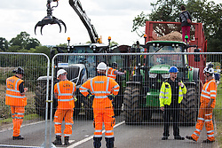 A police officer speaks to HS2 workers after an anti-HS2 activist had occupied a trailer transporting wood chip in order to try to prevent or delay tree felling alongside the Fosse Way in connection with the HS2 high-speed rail link on 24th August 2020 in Offchurch, United Kingdom. The controversial HS2 infrastructure project is currently expected to cost £106bn and will destroy or significantly impact many irreplaceable natural habitats, including 108 ancient woodlands.