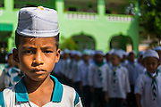 10 JULY 2013 - PATTANI, PATTANI, THAILAND: A boy stands outside during an assembly at a private Muslim school in Pattani, Thailand. Many Muslim parents prefer to send their children to Muslim private schools because they are safer (public schools have been attacked by Muslim insurgents), the Muslim schools teach an Islam centric curriculum and teach what many in Pattani consider a more accurate version of Pattani history.   PHOTO BY JACK KURTZ