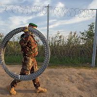 Soldier carries a section of razor wire to finish the last few meters of the fence on the border between Serbia and Hungary near Roszke (about 174 km South of capital city Budapest), Hungary on September 14, 2015. ATTILA VOLGYI