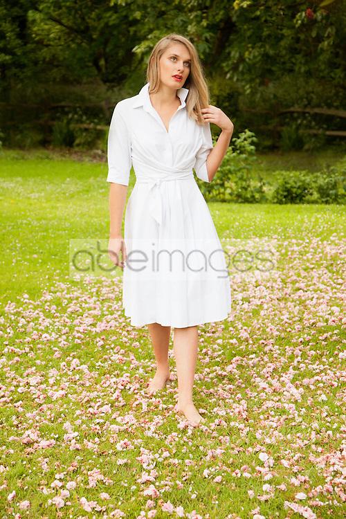 Young Woman in Shirt dress Walking Barefoot in Garden