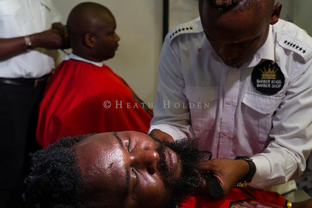 A customer has his beard trimmed in a popular Westlands barber shop in Nairobi Kenya on Thursday 19th of September.
