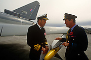 A Royal Navy Admiral and an RAF Air Chief Marshal inspect a missile on the wing tip of a Eurofighter (now called Typhoon) fighter jet. VIPs and special military guests celebrate the success of the aviation defence project at the BAE Systems factory at Warton, Lancashire, England. The Eurofighter Typhoon is a twin-engine, canard-delta wing, multirole combat aircraft, designed and built by a consortium of three companies. Its maiden flight took place on 27 March 1994 watched by VIPs from UK industry and military.