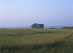 Sunset in Southampton, NY over grassland, bay and boathouse