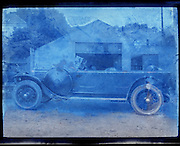 deteriorating image of car in front of barn early 1900s