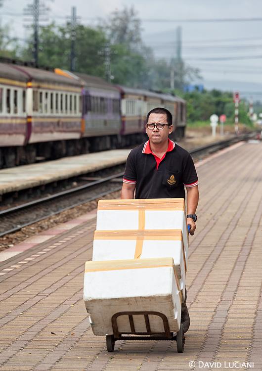 A man carrying boxes at Hua Hin train station.