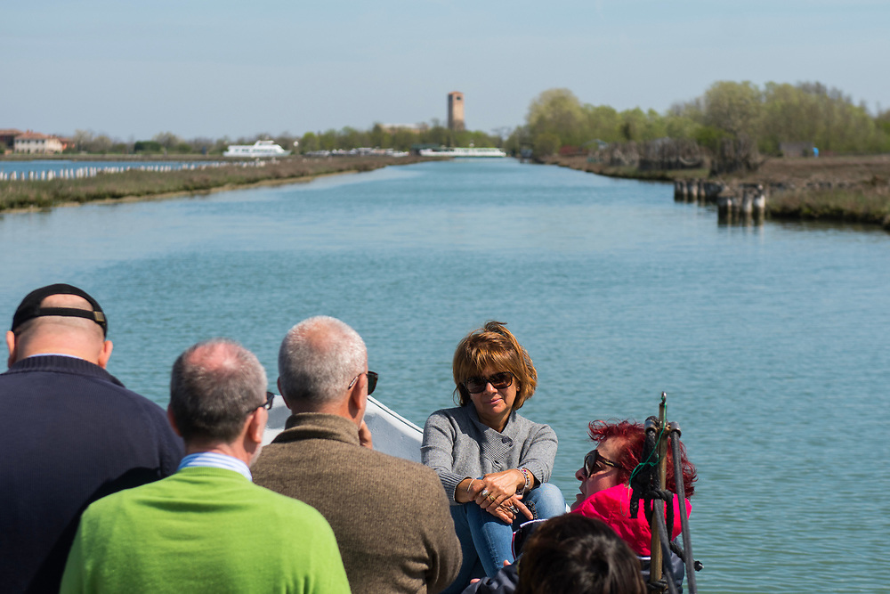 """VENICE, ITALY - APRIL 2018. <br /> Tourists sail along a canal close to Torcello Island during the fishing tour of the 'Moeche' in the northern lagoon of Venice. After visiting Emiliano's """"cason"""", the typical temporary house of the fishermen of the Venetian lagoon, the next stop will be in another """"cason"""", where they will taste some fresh cooked moeche."""