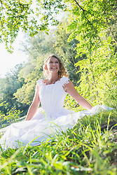 Smiling beautiful bride sitting by lake, Bavaria, Germany